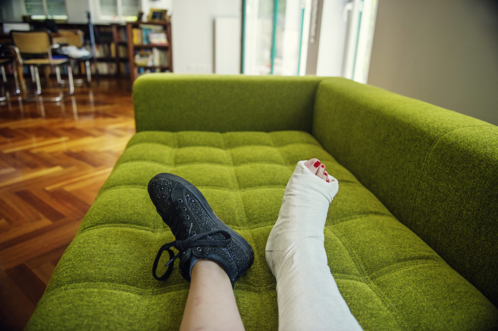 Girl with cast / splint on sofa of private home